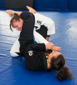 female jiu-jitsu student in black gi practies armbar on woman student in white gi